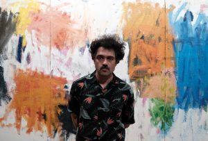 Artist Jorge Nava standing infront of his painting