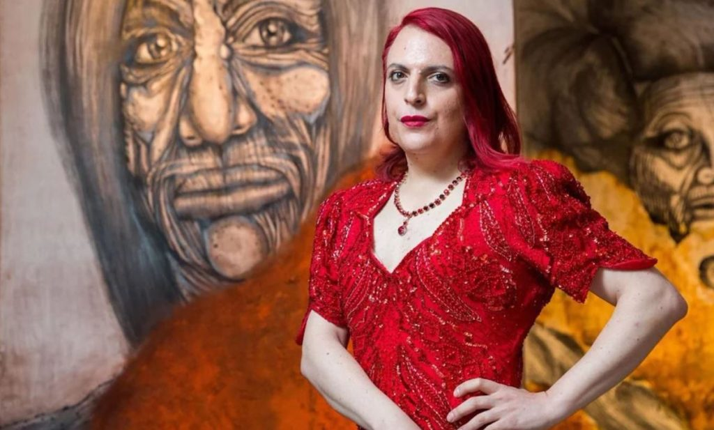 Portrait in front of a painting by Roey Victoria Heifetz for the Stonewall 50th Anniversary Exhibition at GlogauAIR July 2019