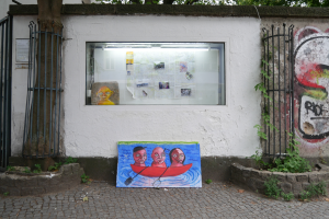 This is an image of a work by the Australian artist Shae Gregg, displayed in the showcase window of the GlogauAIR artist residency in Kreuzberg, Berlin. In it, a map of Berlin is displayed, along with photographs, trash and a painting of a face on an old upholstered chair seat. In front of the dislay case stands a painting on a piece of wood of three people in a boat.