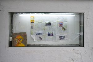 This is an image of a work by the Australian artist Shae Gregg, displayed in the showcase window of the GlogauAIR artist residency in Kreuzberg, Berlin. In it, a map of Berlin is displayed, along with photographs, trash and a painting of a face on an old upholstered chair seat.