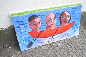 A paiting on a panel of found wood stands against the wall on a street in Kreuzberg, Berlin.
