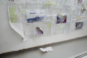 A detail of an installation by Shae Gregg in the showcase at GlogauAIR in Kreuzberg, Berlin. It shows part of a map of Berlin on which photograhs have been placed, as well as trash like a chocolate bar wrapper and a packet of cigarettes.