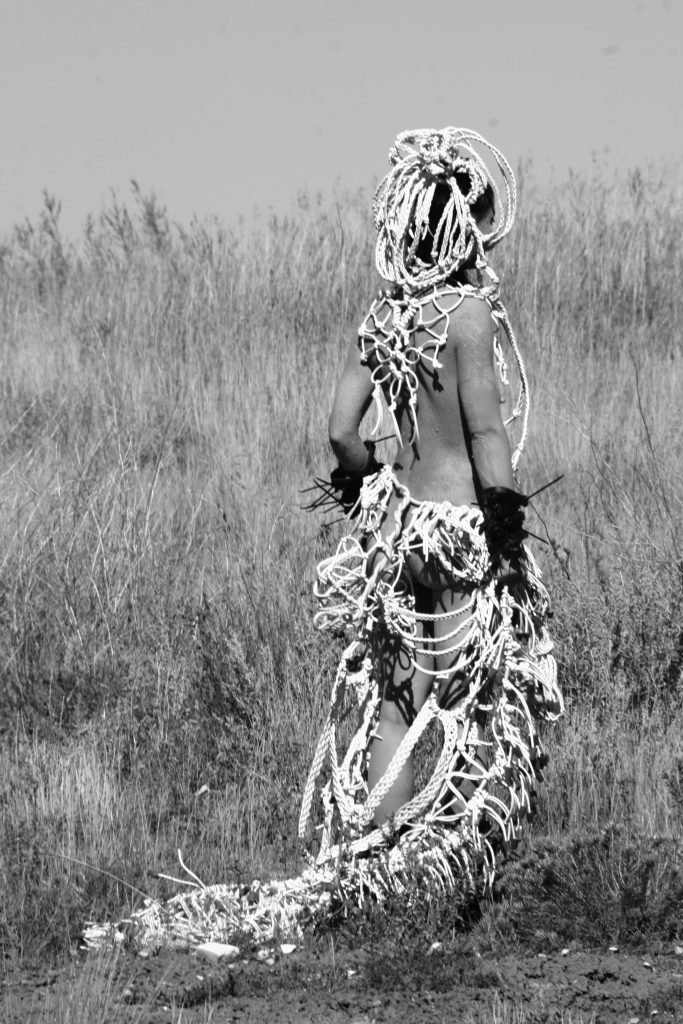 Photograph of costume being worn by woman stood facing away from camera by artist Astrid Lloyd, resident at GlogauAIR 2019