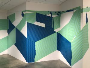 Photograph of intersecting lines placed onto a white wall by artist Ian Jehle, resident at GlogauAIR 2019