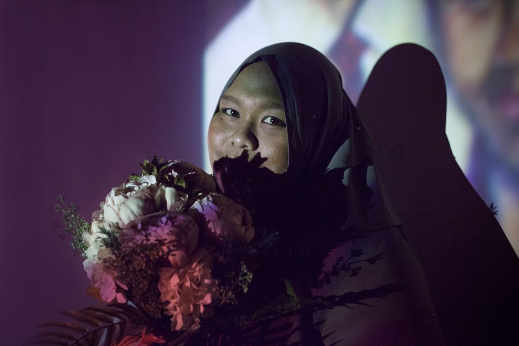 Photograph of girl holding flowers by artist Charmaine Poh. Aini holds flowers as she looks into the camera.