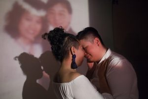 Photograph by Charmaine Poh, resident artist at GlogauAIR 2019. Fi and Liting embrace in front of a wedding portrait of Liting's parents. They envision walking down the aisle to Young Volcanoes by Fall Out Boy.
