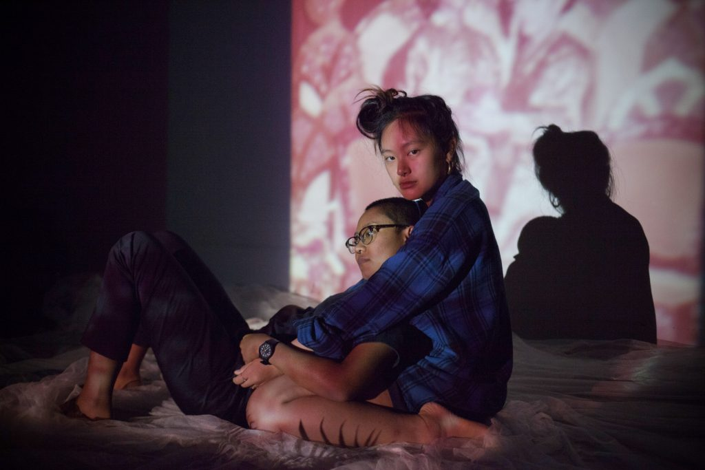 Photograph by Charmaine Poh, resident artist at GlogauAIR 2019. Sy and Jonit sit in front of a portrait of Sy's parents. It's Jonit's first relationship, and she doesn't identify with any particular sexual identity.