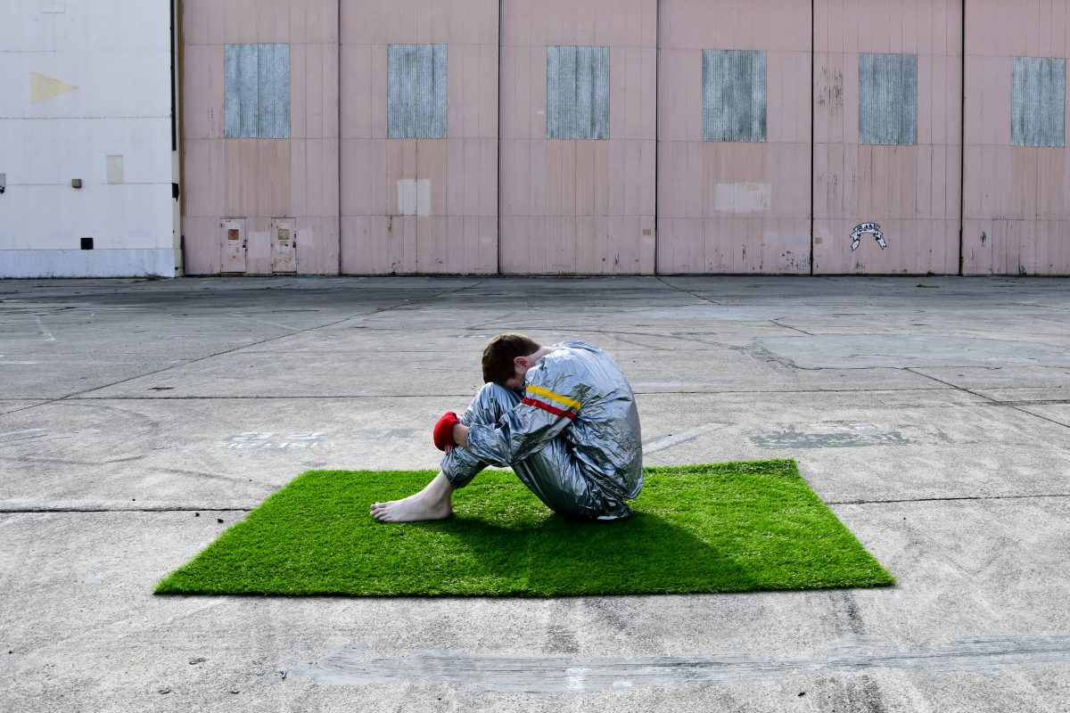 Photograph of a person sat on a square of grass surrounded by an industrial background and concrete ground, by artist Kyle Giacomo, resident at GlogauAIR October 2019.