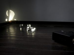 Photograph of light being projected through small cut outs arranged on the floor in front of a corner of a room. By artist Marcos Kaiser, resident artist at GlogauAIR January 2020