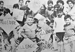 Black and white photograph of children holding kites which say Allende