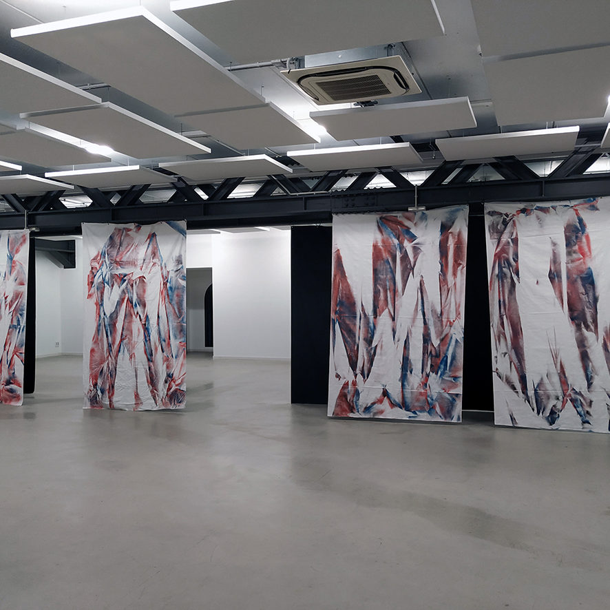 Photograph of several paintings by artist Ismael Iglesias in a gallery space