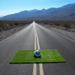 Photograph of a foil ball on a square of grass placed on a long road which disappears into landscape by artist Kyle Giacomo, resident artist at GlogauAIR 2019